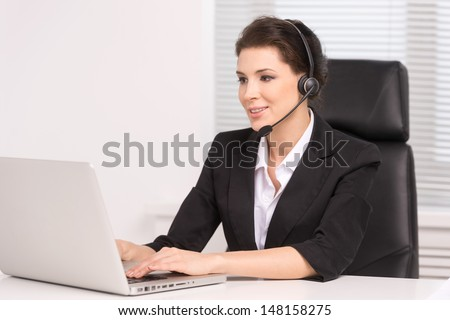 Customer service representative at work. Confident middle-aged woman in headphones sitting at her working place and smiling