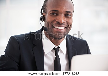 Customer service representative. Cheerful young African man in formalwear and headset working on laptop and smiling at camera - stock photo