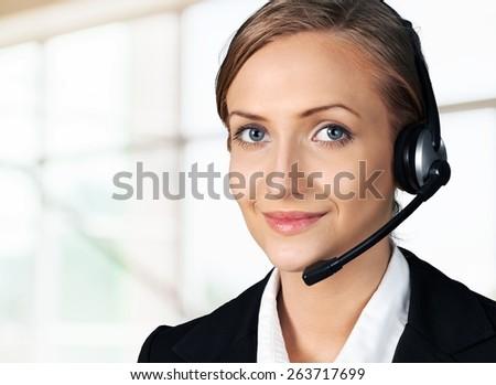 Customer Service Representative. Closeup of a female call center employee smiling - stock photo