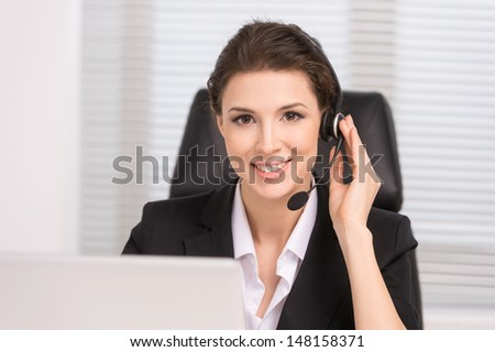 Customer service representative. Confident middle-aged woman in headphones sitting at her working place and smiling - stock photo
