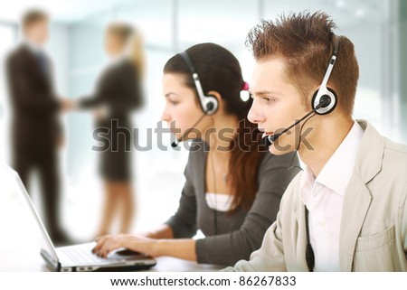 Customer service representatives in modern office with  headsets. Business people shaking hands on background - stock photo