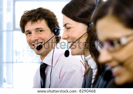 Customer service team working in headsets. Focus placed on smiling man in back. - stock photo