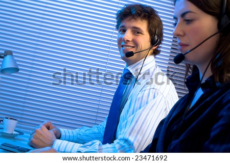 Customer service team working in headsets, late night at office. Focus placed on smiling man in back. - stock photo