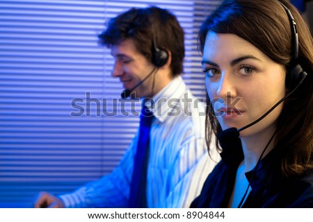 Customer service team working in headsets, late night at office. Focus placed on woman in front. - stock photo