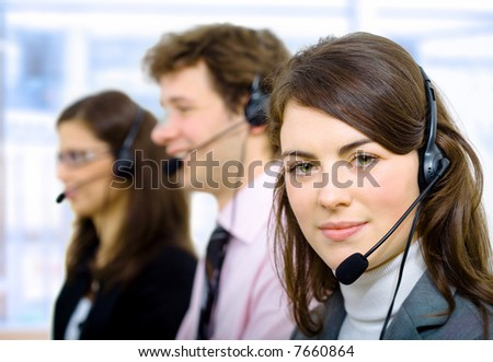Customer service team working in headsets, smiling. - stock photo