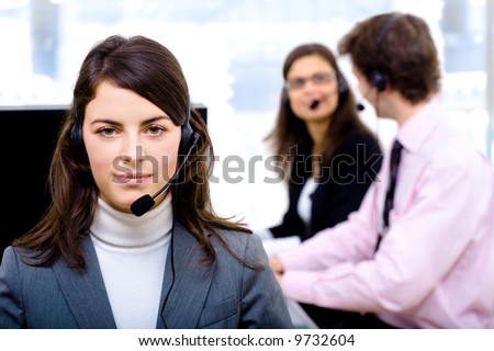 Customer service team working in headsets, smiling. Woman in front. - stock photo