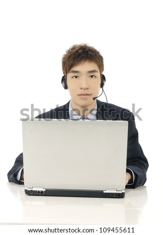 Customer services man at his desk on a laptop computer - isolated over a white background - stock photo