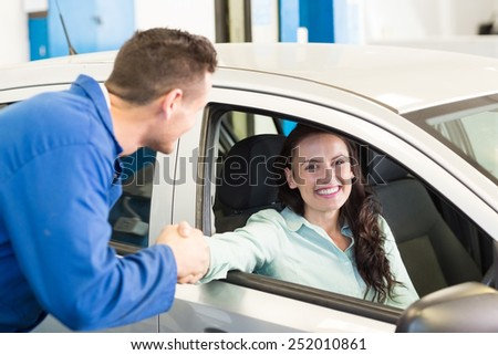 Customer shaking hands with mechanic at the repair garage - stock photo