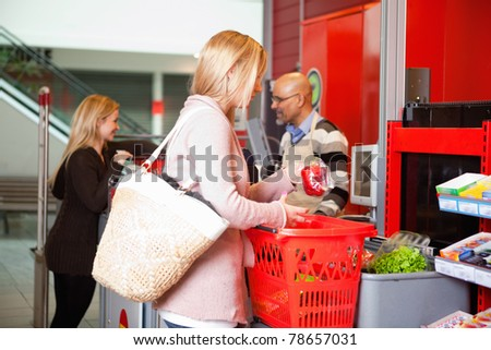 Customer shopping in supermarket with people in the background - stock photo