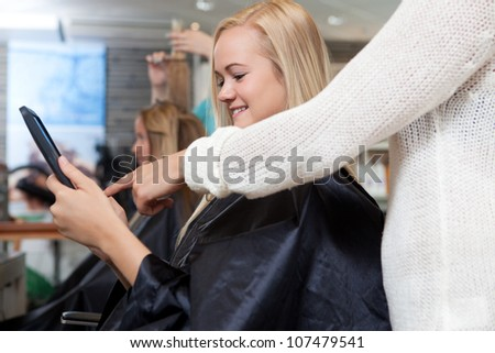 Customer showing hair dresser an image on a digital tablet.