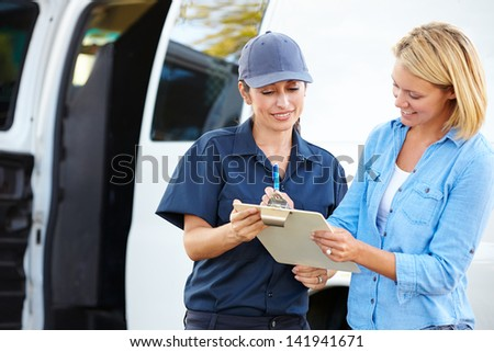 Customer Signing For Delivery From Female Courier - stock photo
