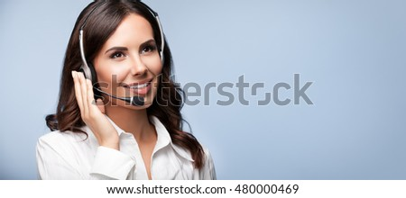 Customer support female phone operator in headset, with copyspace, on grey background. Consulting and assistance service call center.