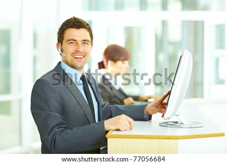 Customer support operator smiling in an office and touching the computer screen