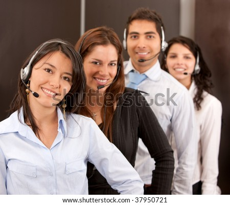 Customer support operators in an office smiling - stock photo