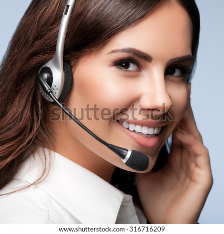 customer support phone operator in headset, against grey background. Consulting and assistance service call center. - stock photo
