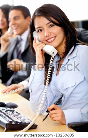 customer support team lead by a friendly girl smiling in an office - stock photo