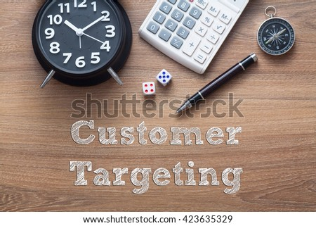Customer Targeting written on wooden table with clock,dice,calculator pen and compass - stock photo