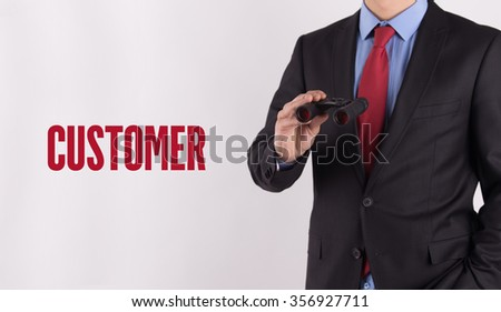 CUSTOMER text on white background with businessman holding binoculars - stock photo