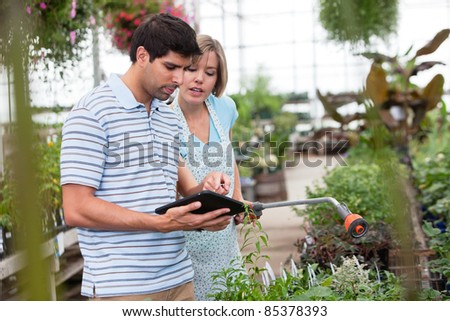 Customer using a digital tablet in greenhouse