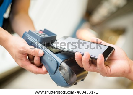 Customer using cellphone for pay by NFC technology - stock photo