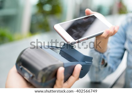 Customer using cellphone to pay with NFC technology  - stock photo
