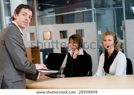 Customer waiting at the frontdesk, checking his appointment in his laptop - stock photo