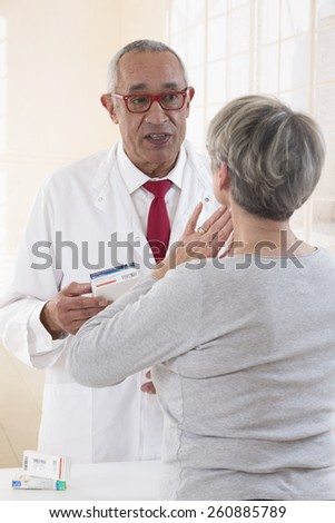 Customer with flu and sore throat in pharmacy talking to a pharmacist - stock photo