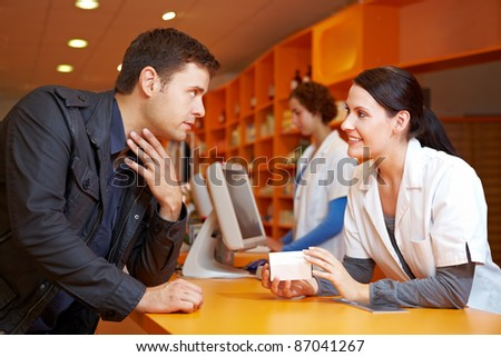 Customer with flu in pharmacy talking to a pharmacist - stock photo