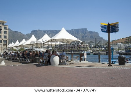 CUSTOMERS AT A CAPE TOWN CAFE OVERLOOKING TABLE MOUNTAIN - CIRCA 2014 - On the V&A Waterfront Cape Town tourists enjoying the harbour view from their tables.