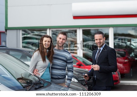 Customers buying a car in a dealership - stock photo