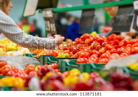 Customers selecting tomatoes in supermarket - stock photo