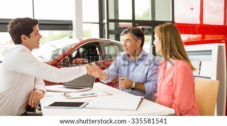 Customers signing some important documents at new car showroom - stock photo