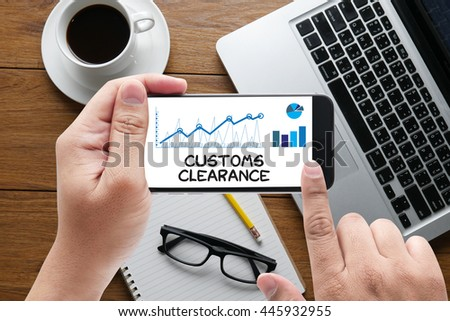 Customs Clearance message on hand holding to touch a phone, top view, table computer coffee and book - stock photo