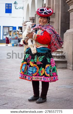 CUSZO, PERU - MARCH 18, 2015: Peruvian woman in traditional dresses pose  for tourists in Cuzco, Peru - stock photo
