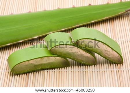 Cut and whole aloe vera leaf on bamboo mat - stock photo