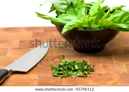 Cut and whole basilicum leafes on cutting board