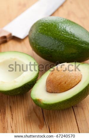 cut avocado on wooden table - stock photo