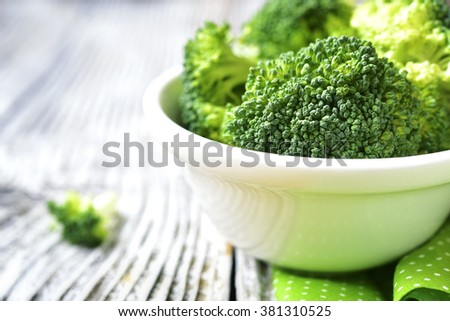 Cut broccoli in a white bowl on rustic background. - stock photo