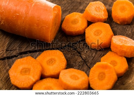 Cut carrot on a wooden trunk