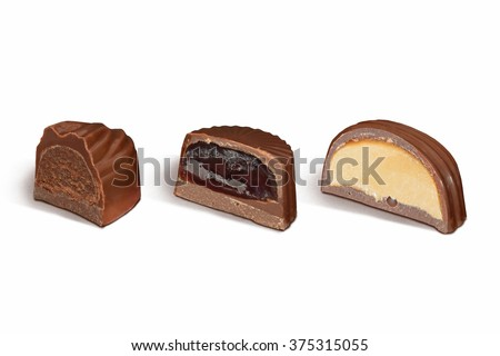 cut chocolate candies with different fillings on white background - stock photo