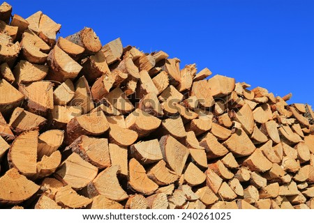 Cut, chopped and stacked up dry firewood against clear blue sky. - stock photo