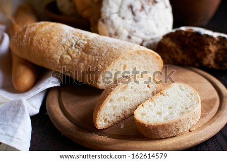Cut ciabatta bread on the board with selective focus - stock photo