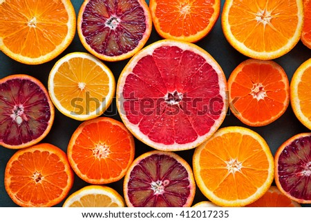 cut citrus fruits on the Mat on black background - stock photo