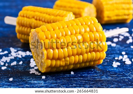 Cut corn on the cob on a stick surrounded by white crystals - stock photo