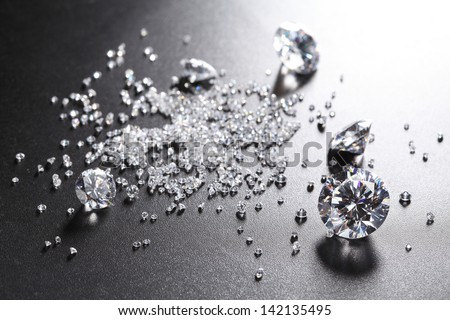 cut diamonds on shiny black surface  - stock photo