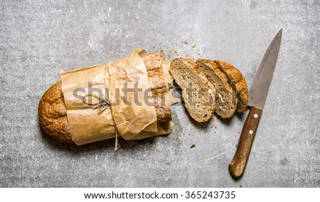 Cut fresh bread with a knife.  On the stone table. Top view - stock photo
