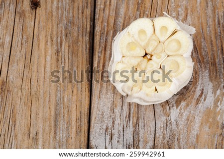 Cut garlic on old wood textured table - stock photo