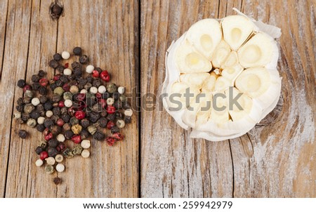 Cut garlic with color pepper spice on old wood textured table - stock photo