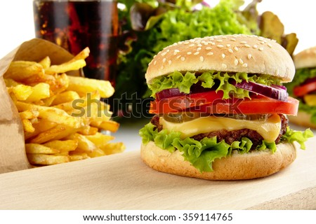 Cut image of big cheeseburger with french fries and glass of cola on wooden board