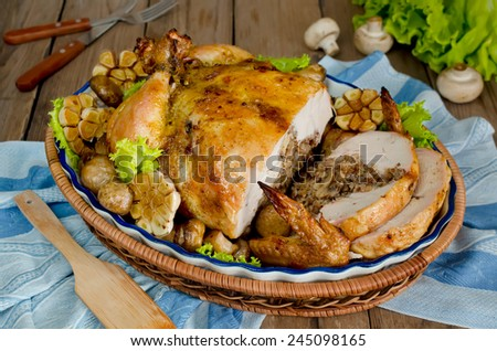 Cut into portions of fried chicken stuffed with buckwheat and mushrooms. On the wooden table - stock photo